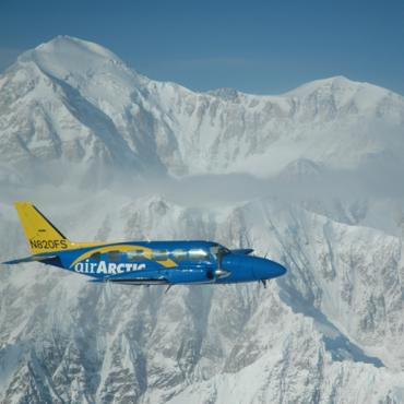 Air Artic plane over snowy peaks AK